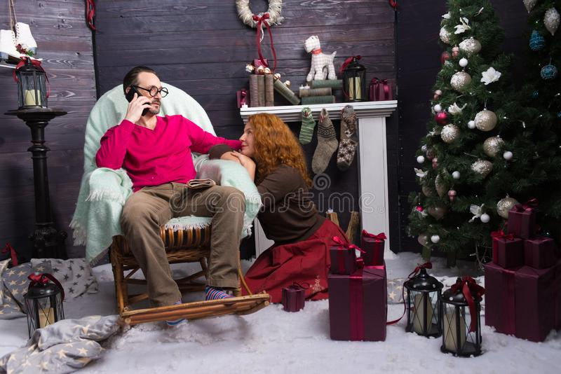 Two people sitting in New Year interior near the fireplace. Calm men sitting in the rocking chair and talking on the phone while loving women looking at him royalty free stock photo