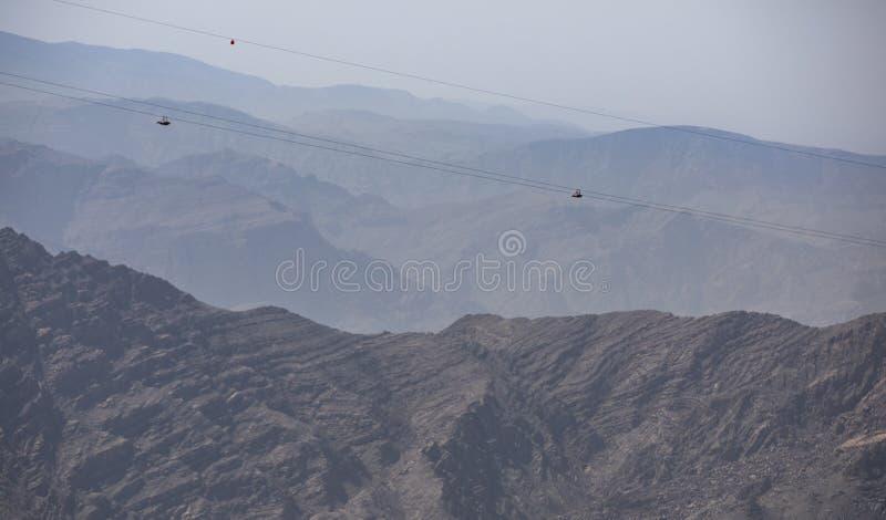 Adventure sport - zipline slide down Jebel Jais mountain. Two people sliding down Jebel Jais Mountain via world`s longest zip line royalty free stock photo