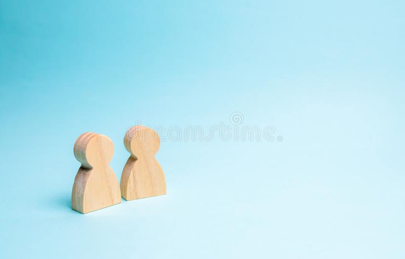 Two people stand together and talk. Two wooden figures of people conduct a conversation on a blue background. Communication, stock photos