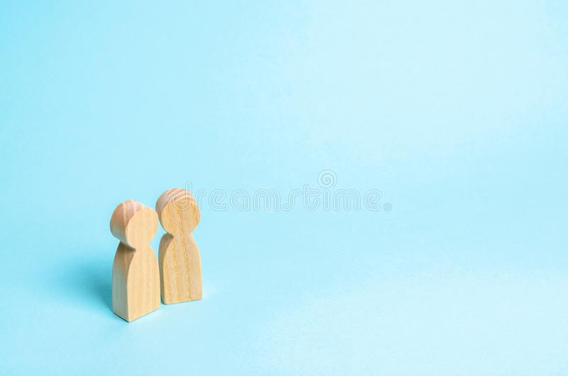 Two people stand together and talk. Two wooden figures of people conduct a conversation with a blue background. Communication royalty free stock image
