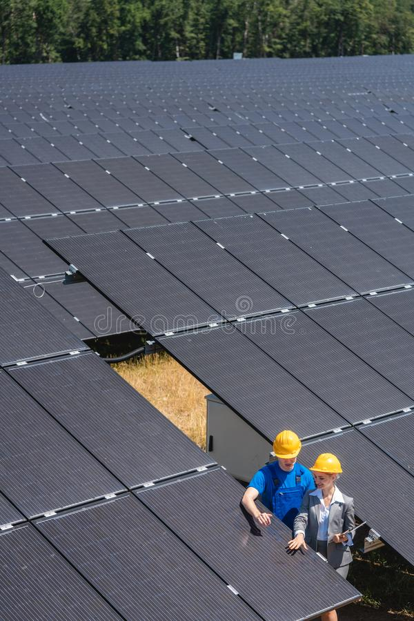 Two people standing amid solar cells in a power plant royalty free stock image