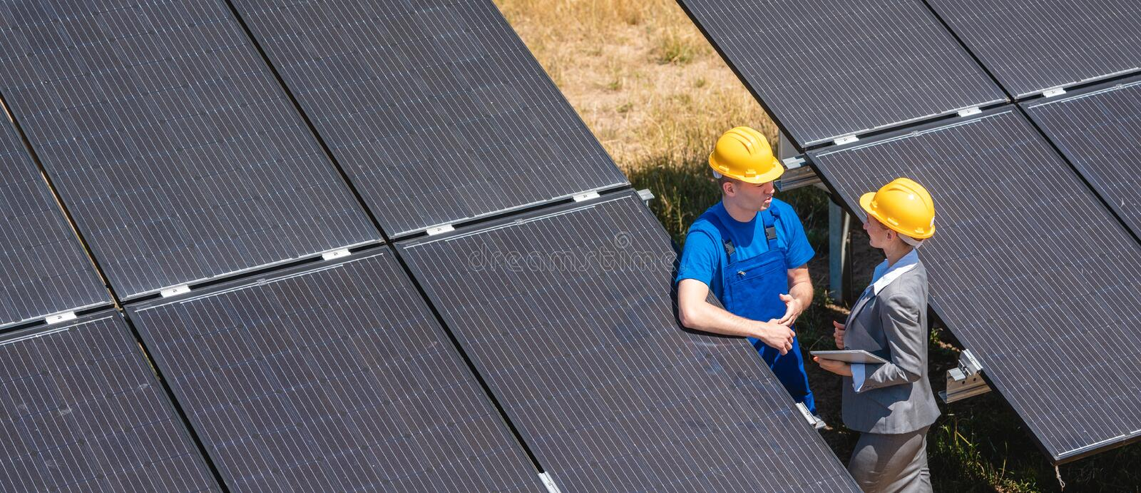 Two people standing amid solar cells in a power plant royalty free stock photography