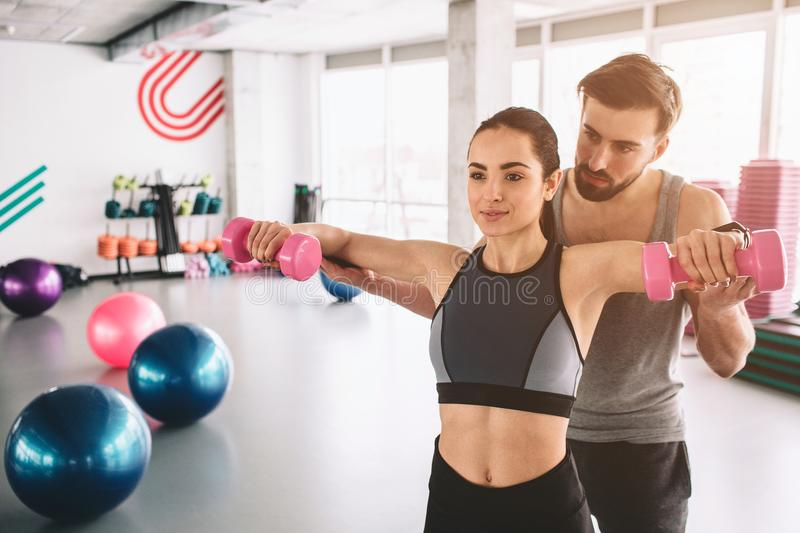 Two people are standing in the finess room. The guy is helping his girfriend to do push ups with dumbells. Cut view. stock image