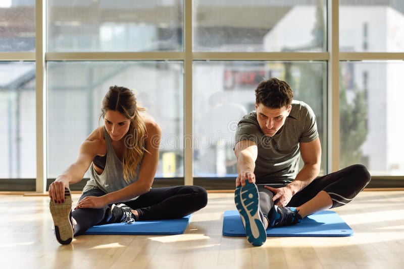 Two people streching their legs in gym. royalty free stock photography