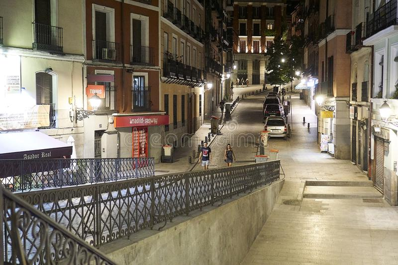Two people taking a walk on Madrids street at night. MADRID, SPAIN - 13. July 2017: Two people taking a walk on Madrids street at night stock photo