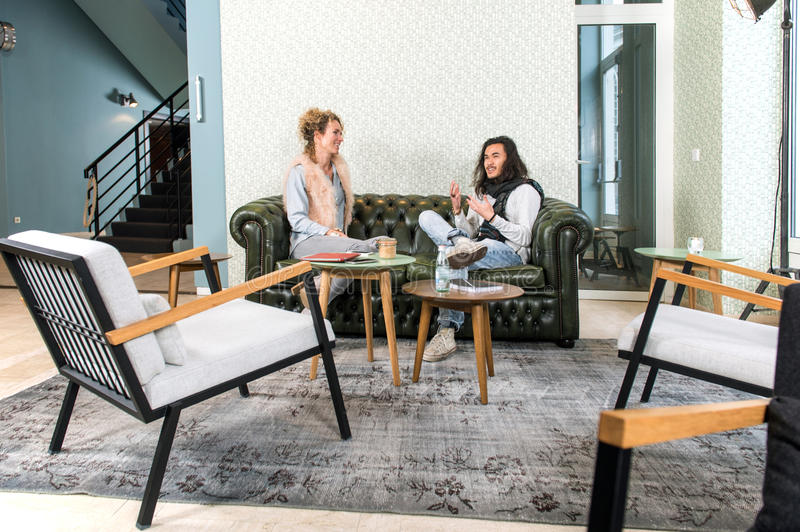 Two people talking in a lounge. Two people, a men and a woman, sitting on a chesterfield couch in a trendy, retro styled, lobby of a theater, talking vividly royalty free stock photography