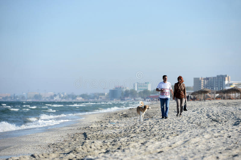 Two people walk with a dog royalty free stock photography