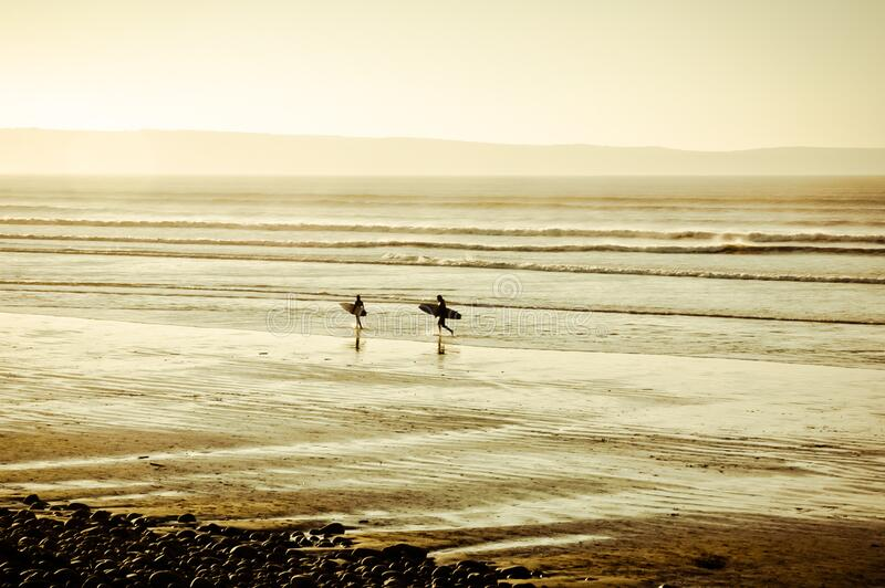 Two people walk to the beach from the sea after surfing in the ocean during sunset stock photo