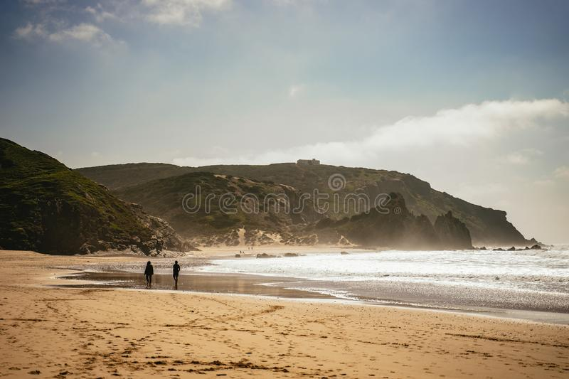 Two people walking along a sandy beach stock photos