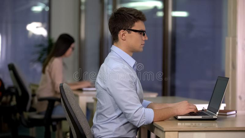 Two people working on laptop in big office, technical support, service center stock photo