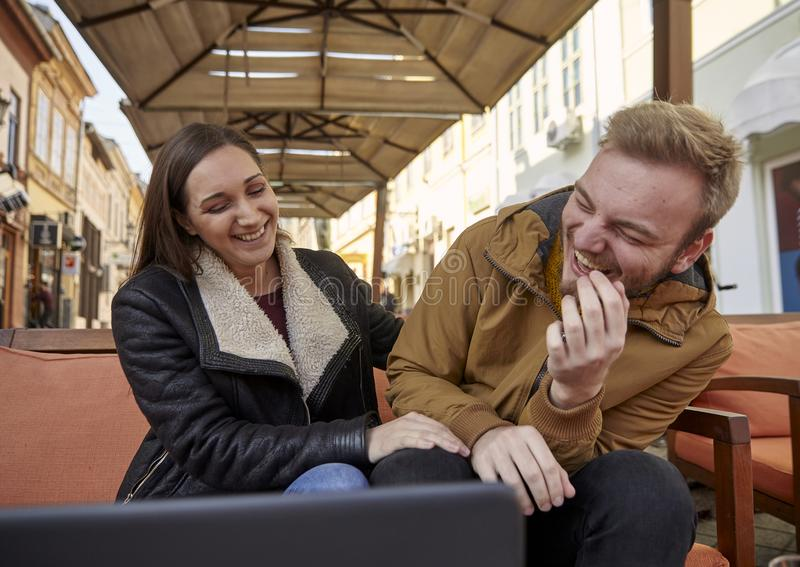 Two people, 20 - 29 years old, candid laughing out loud. sitting in a cafe royalty free stock images