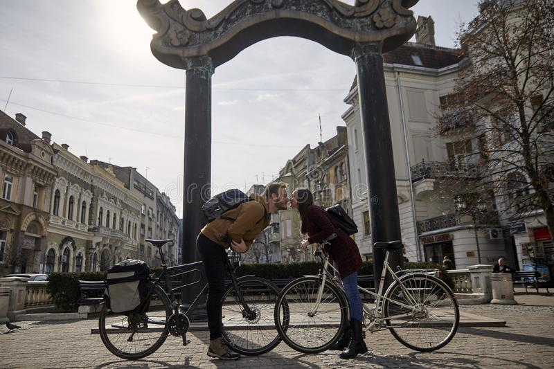 Two people, 20-29 years old, romantic couple looking at each other head to head, while posing, leaning with their bicycles. About to kiss. beautiful city royalty free stock images