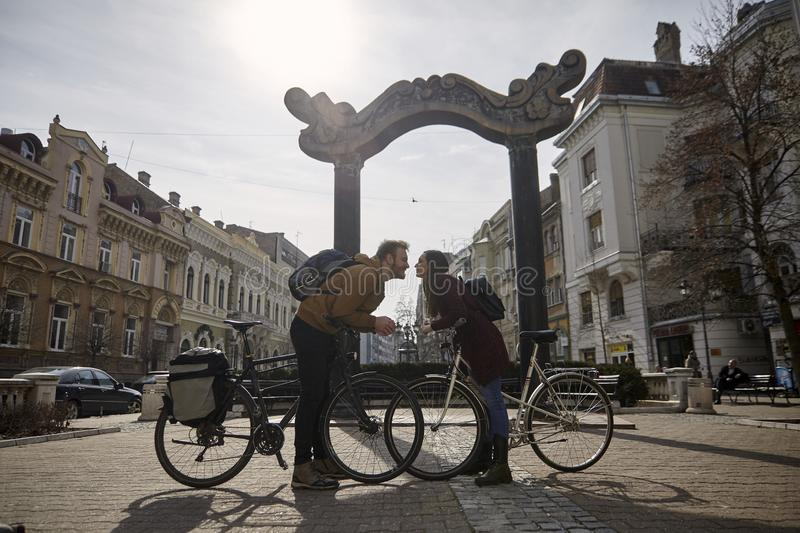 Two people, 20-29 years old, romantic couple looking at each other head to head, while posing, leaning with their bicycles. About to kiss. beautiful city stock photography