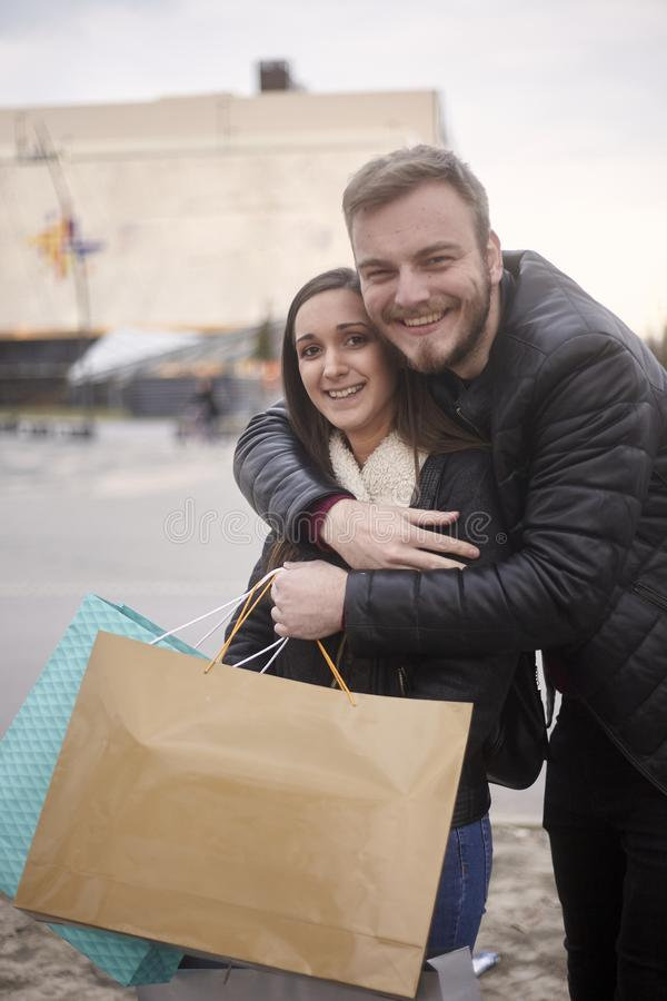 Two people, young adults, 20-29 years old, candid emotion. Friends or couple hugging on a street outside of shopping mall, holding. Shopping bags in hands stock images