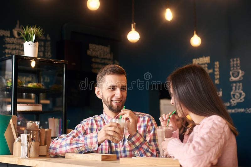 Two people young man and woman in coffee shop enjoying time spending with each other. Romantic acquaintance concept. royalty free stock images