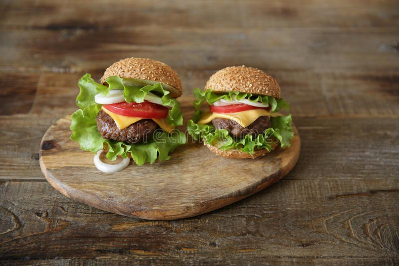 Two perfect hamburger with beef patty, cheese, pickles, tomatoes, onions, lettuce on a wooden rustic background with copy space fo stock images