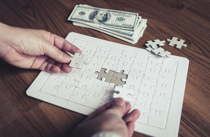 Two person placing two last jigsaws together for team solution concept royalty free stock image