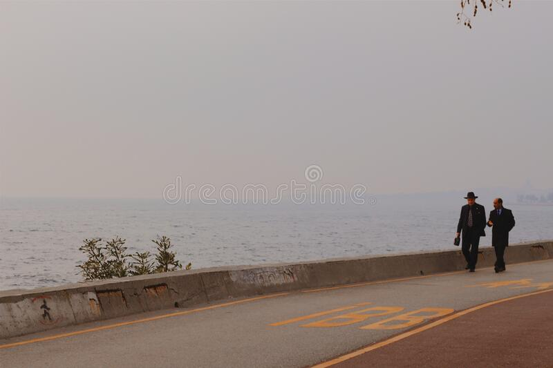 Two Person Walking On A Concrete Road Beside Body Of Water Free Public Domain Cc0 Image