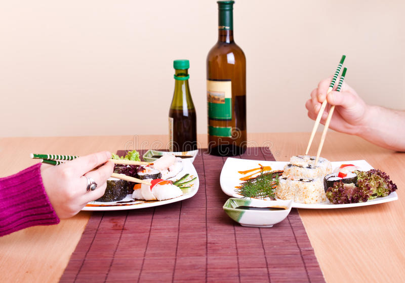 Two persons eating sushi stock photos