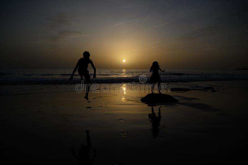Two persons are playing on the beach. A boy and a woman royalty free stock photo