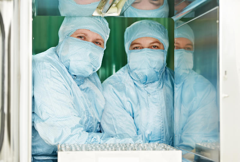 Two pharmaceutical factory workers. Two pharmaceutical factory women workers in protective workwear and masks at pharmacy industry manufacture factory royalty free stock images