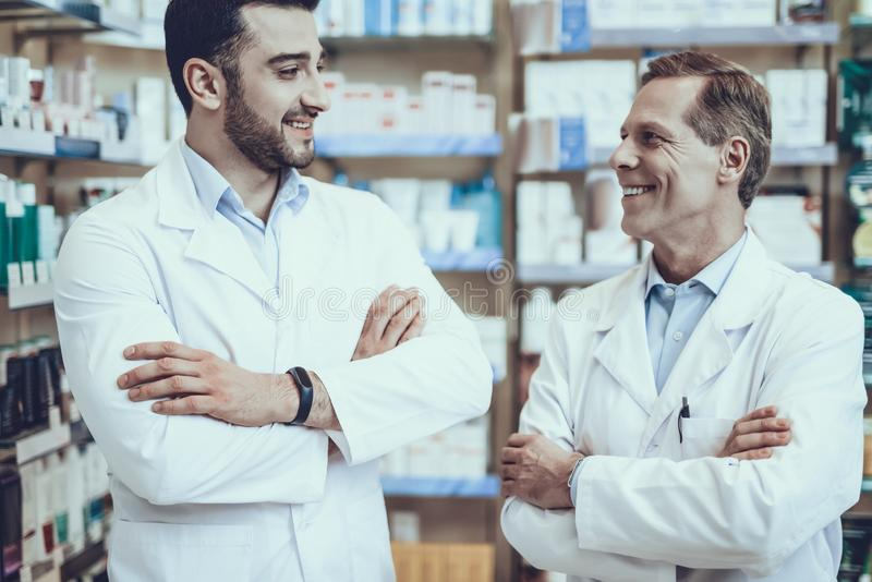 Male pharmacists posing in pharmacy. Two Pharmacists Looking at Each Other. Pharmacists is a Caucasian Adult Man and Young Guy. Men Wearing a Special Medical stock photos