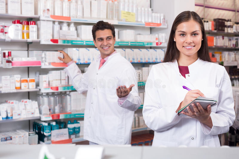 Two pharmacists in modern pharmacy. Portrait of two friendly pharmacists in uniform working in modern pharmacy royalty free stock images