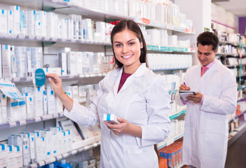 Two pharmacists in modern pharmacy. Two positive smiling pharmacists in white uniform at the work in modern pharmacy royalty free stock image