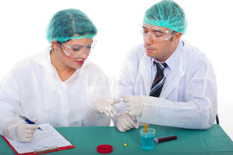 Two pharmacists people examine pills. Two pharmacists laboratory people examine pills and woman taking notes royalty free stock photography