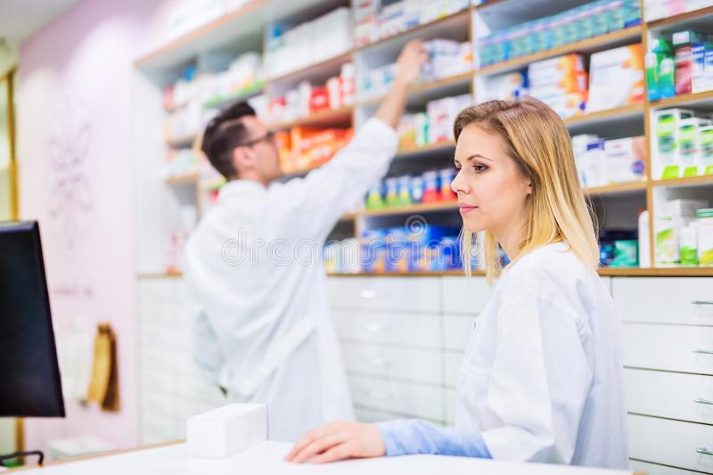 Two pharmacists working in a drugstore. Two friendly pharmacists working in a drugstore stock images