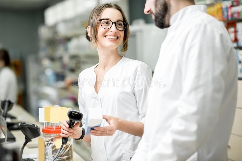 Pharmacists working in the pharmacy store. Two pharmacists working at the paydesk selling medications in the pharmacy store stock images