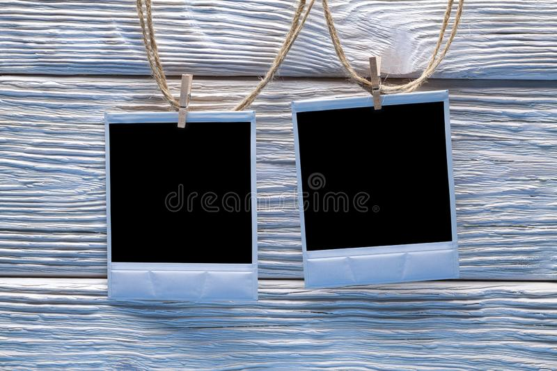 Two photo frames on ropes and wooden wall background stock photos