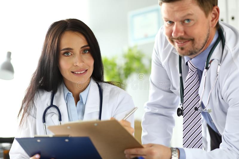 Two physicians discussing important documents clipped to pad royalty free stock photography