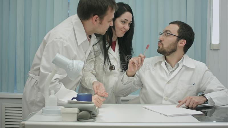 Two physicians in good mood discussing something in internet at medical center, then comes intern royalty free stock photography