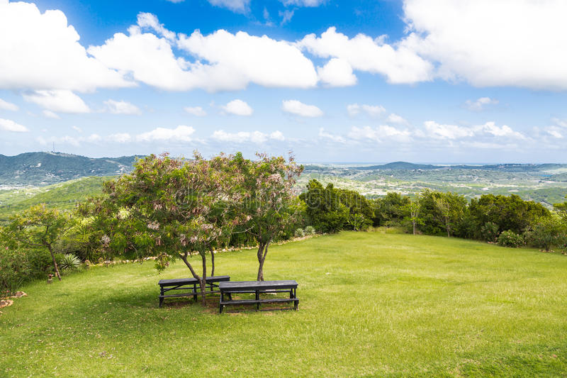 Download Two Picnic Tables Under Small Tees On Hill Stock Photo - Image: 43134386