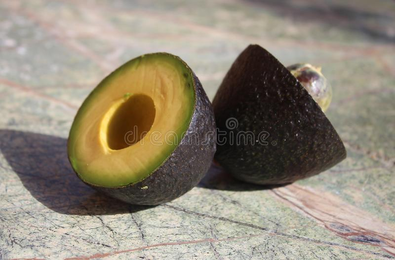 Two pieces of avocado. Avocado cut into two parts. On the rain forest stone table background stock photos