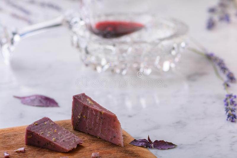Two pieces of Basiron lavender cheese on wooden cutting board, lavender flowers and glass of red wine on white marble worktop. Two pieces of lavender cheese on royalty free stock photos