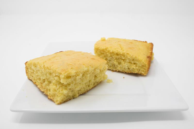 Cornbread on a white plate. Two pieces of cornbread on a white plate against a white background stock photo