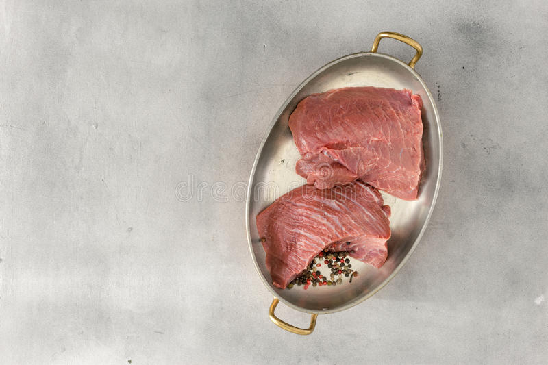Two pieces of fresh beef in pan on stone surface. Two pieces of fresh beef in a pan on a light stone surface with a copy space, top view stock photos