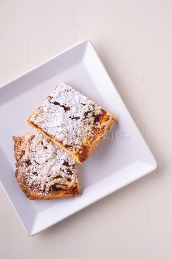 Two pieces of homemade cookies apricot jam powdered sugar in white square plate royalty free stock photography