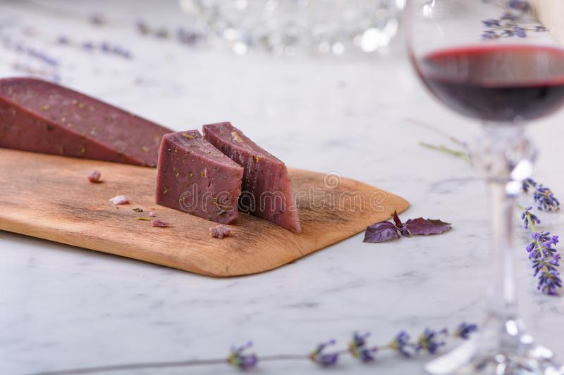 2 pieces of Basiron lavender cheese on wooden cutting board, lavender flowers and glass of red wine on white marble worktop royalty free stock photo
