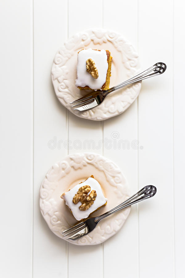 Two Pieces nuts carrot cake with icing cream on ivory color plat. E. Selective focus. Close up. Top view. Copy space.Toned photo stock image