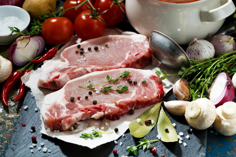 Two pieces of raw pork and ingredients for soup, closeup. Horizontal royalty free stock photos