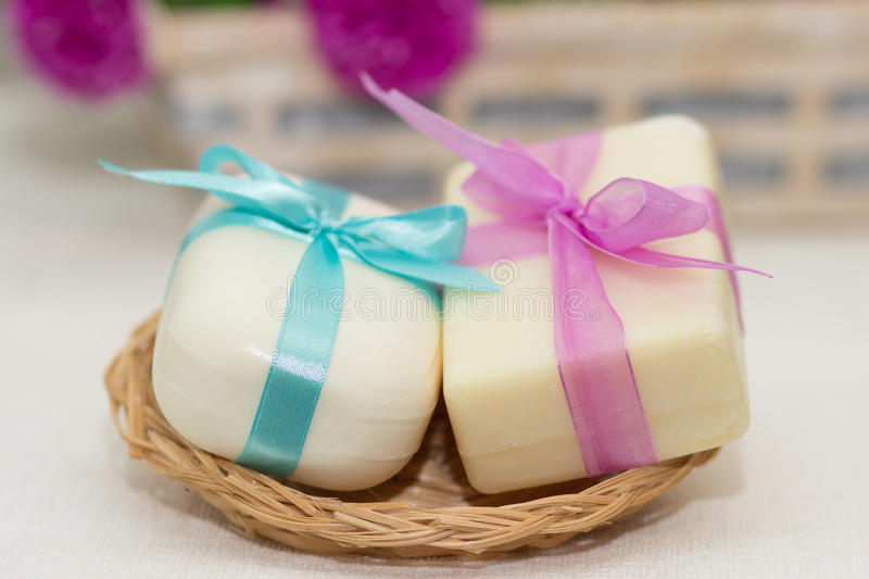 Two pieces of soap with a basket with bows. Blue and purple stock images