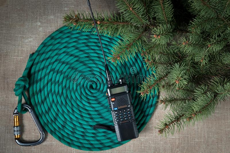 Two pieces of walkie talkie around a climbing rope with a carabiner branch Christmas pine. On a light cloth background stock photo