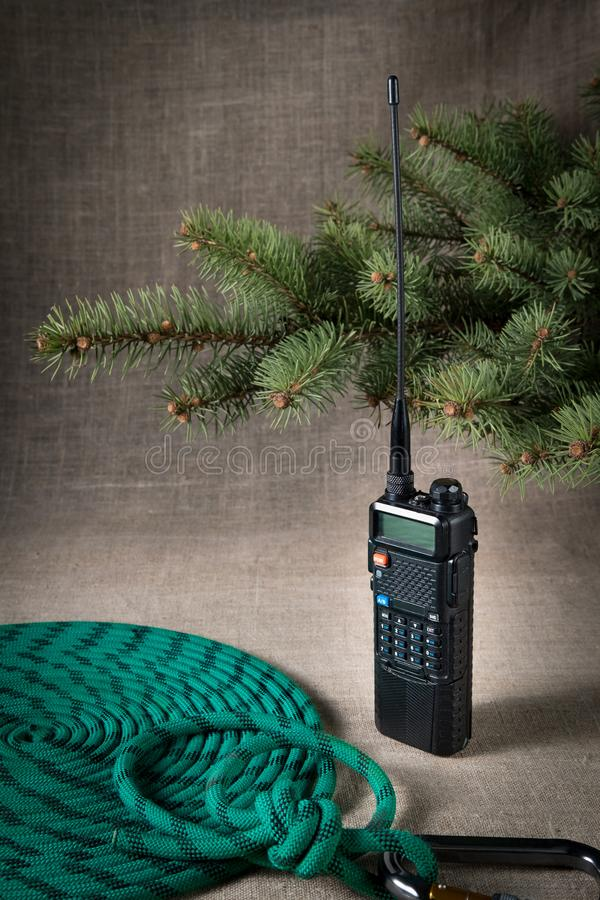 Two pieces of walkie talkie around a climbing rope with a carabiner branch Christmas pine. On a light cloth background stock images