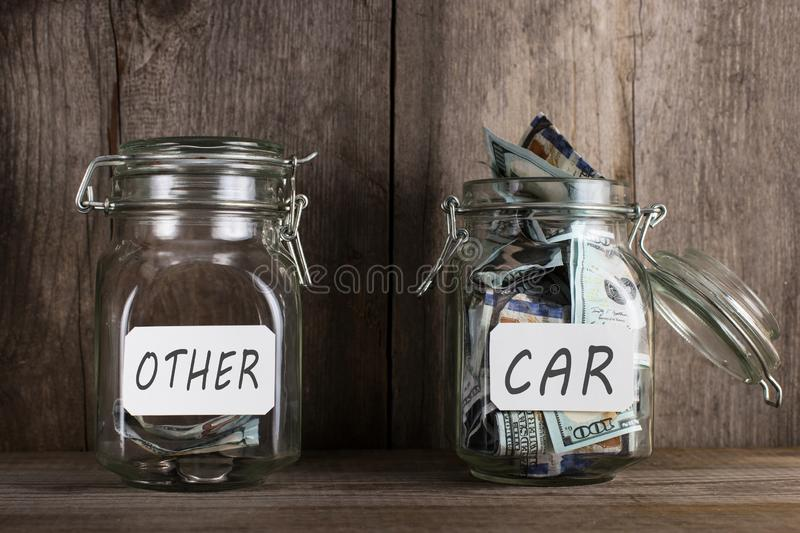 Two piggy banks, with different amounts of money and space for text, stand on a wooden bookshelf. Priority, copy, background, jar, glass, cash, coin, concept stock photos