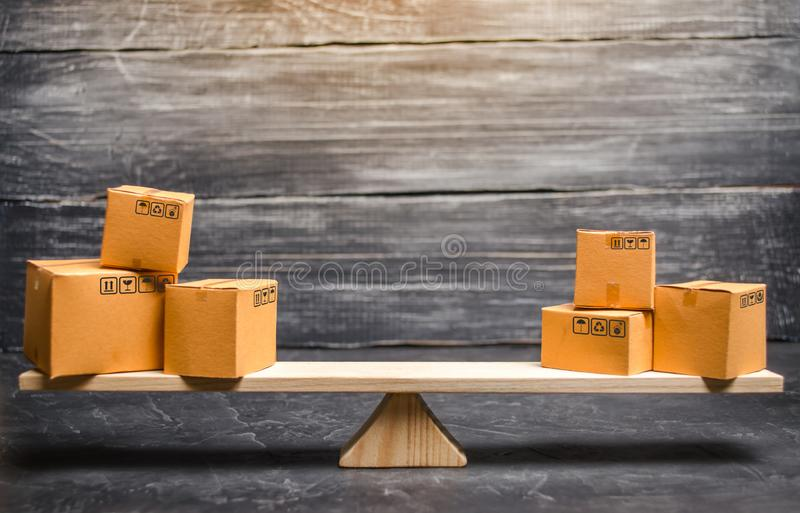 Two piles of boxes on the scales. Trade balance and calculation by barter. Bypassing sanctions, import and export of goods. Trade. Balance. Goods turnover stock image