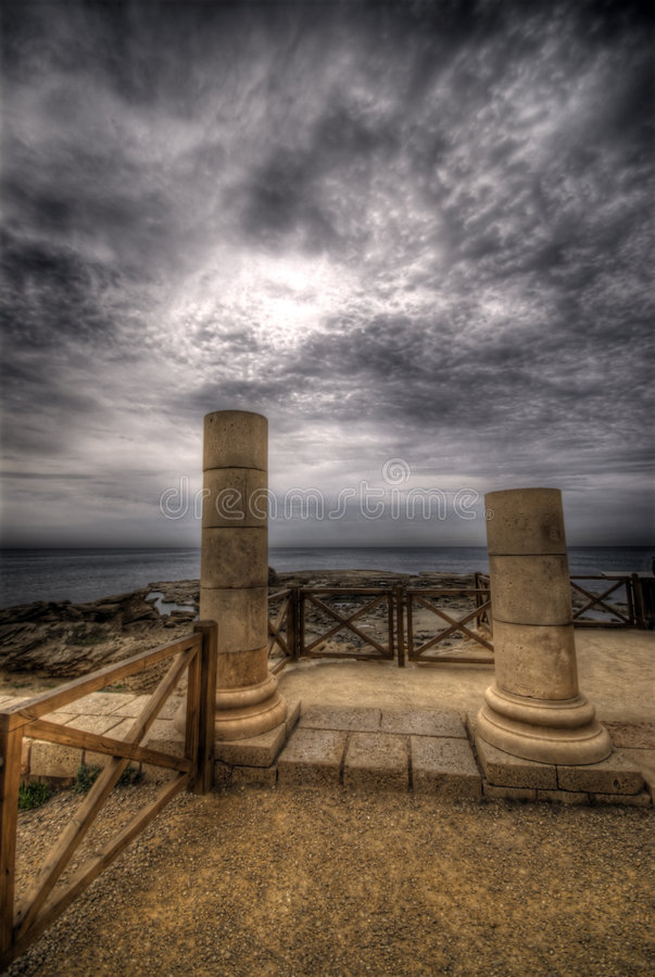 Two pillars. With cloudy dramatic sky royalty free stock photos