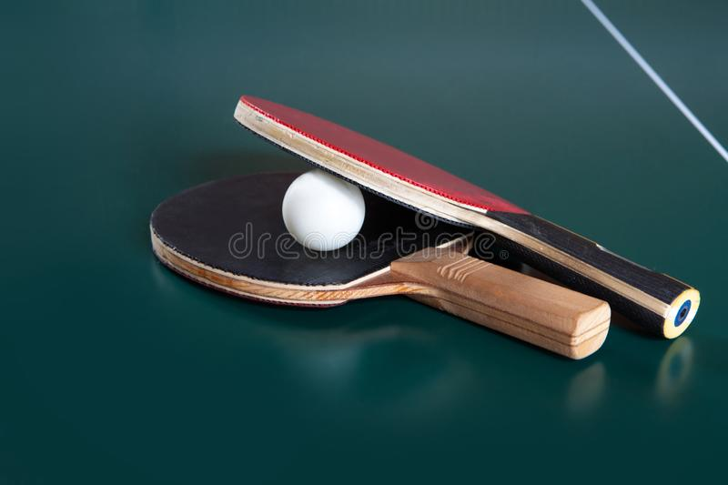 Two ping-pong rackets and a ball on a blue table.  ping-pong net stock image
